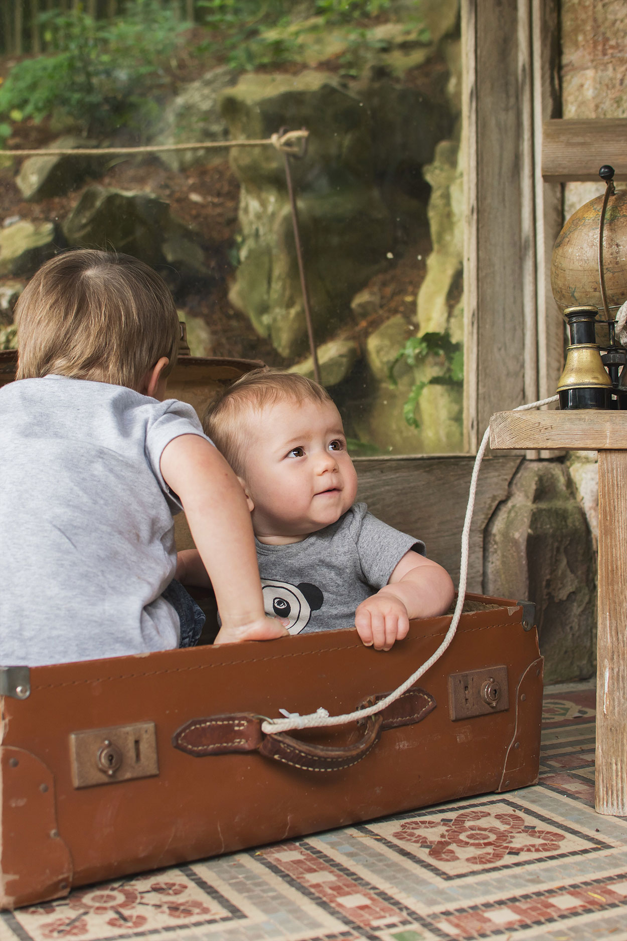 Brothers playing in the suitcase with vintage binoculars and globe in the summer house of the rose garden at Tyntesfield Estate, Hampshire, National Trust