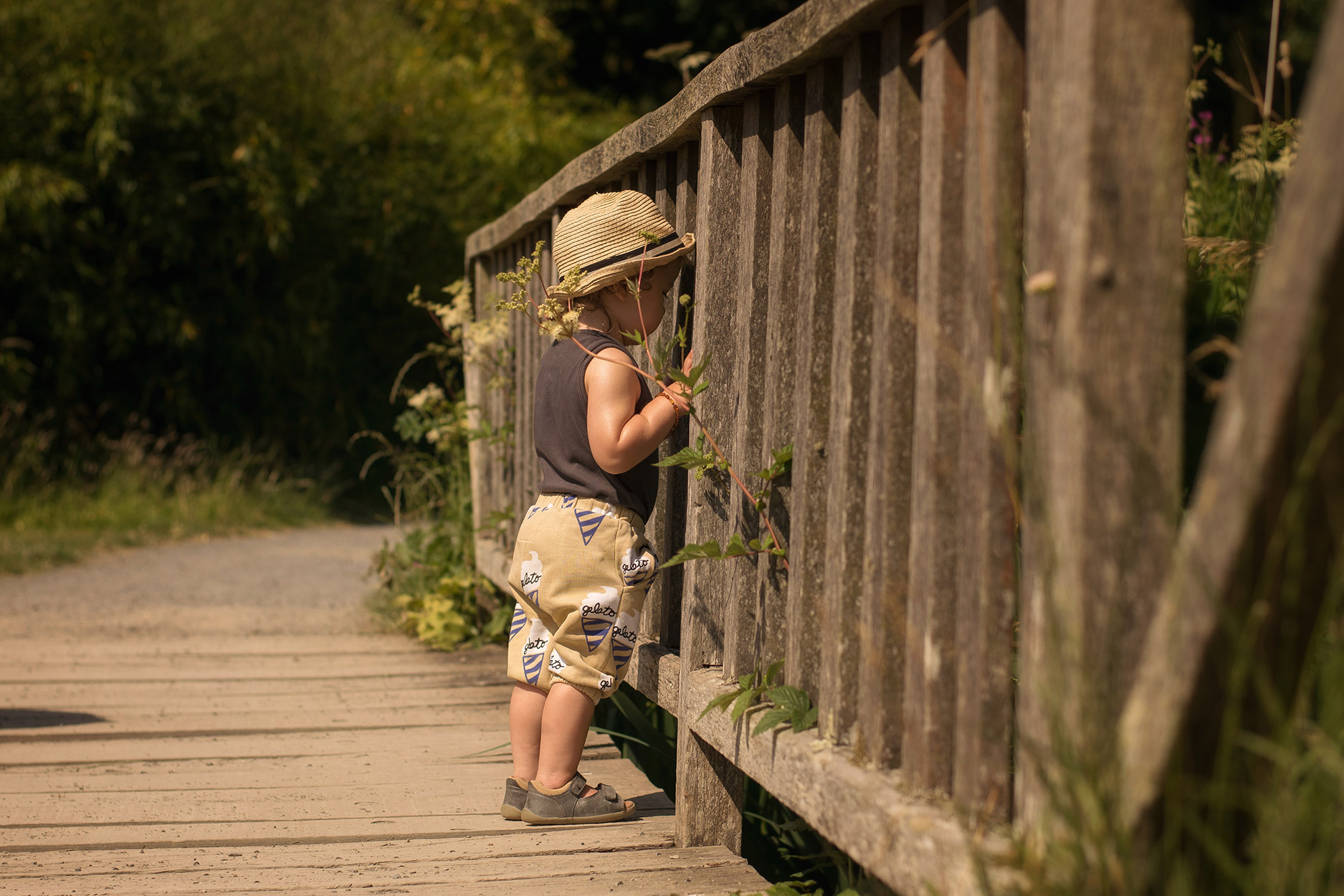 Toddler wearing Hugo Loves Tiki gelato shorts and trilby hat standing on the bridge at Colby Woodland Gardens, National Trust