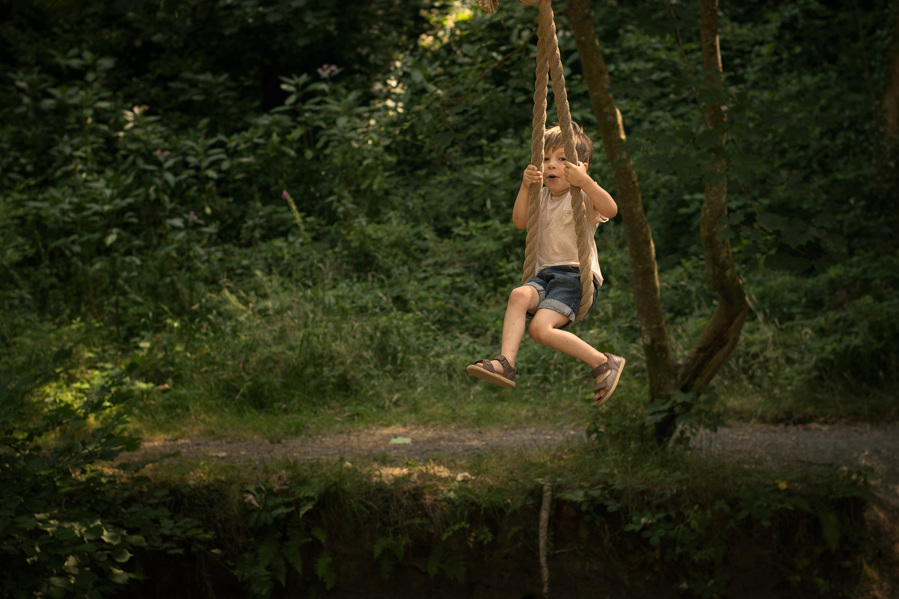 Boy swinging over the river on rope swing laughing wearing trilby hat at Colby Woodland Gardens, National Trust