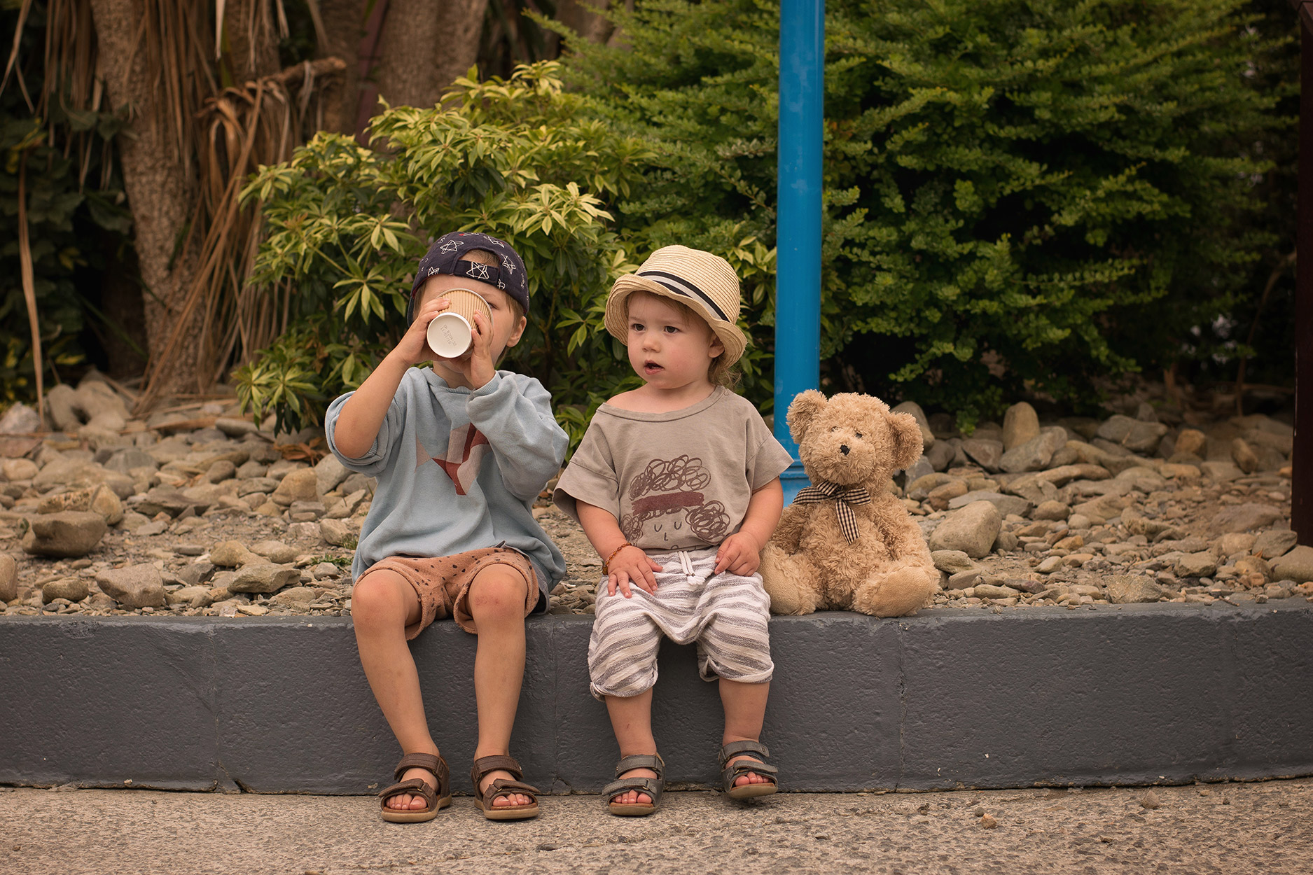 Toddler and pre-schooler brothers wearing Bobo Choses, Maed for Mini and 1+ in the Family clothes and Bobux driftwood sandals at Folly Farm, Wales