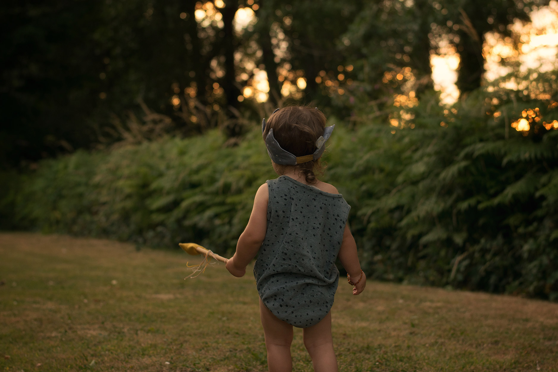 Toddler wearing Made for Mini vest and crown holding magic wand in the golden hour on a warm Summer's evening outside the holiday home in Freshwater East, South Wales