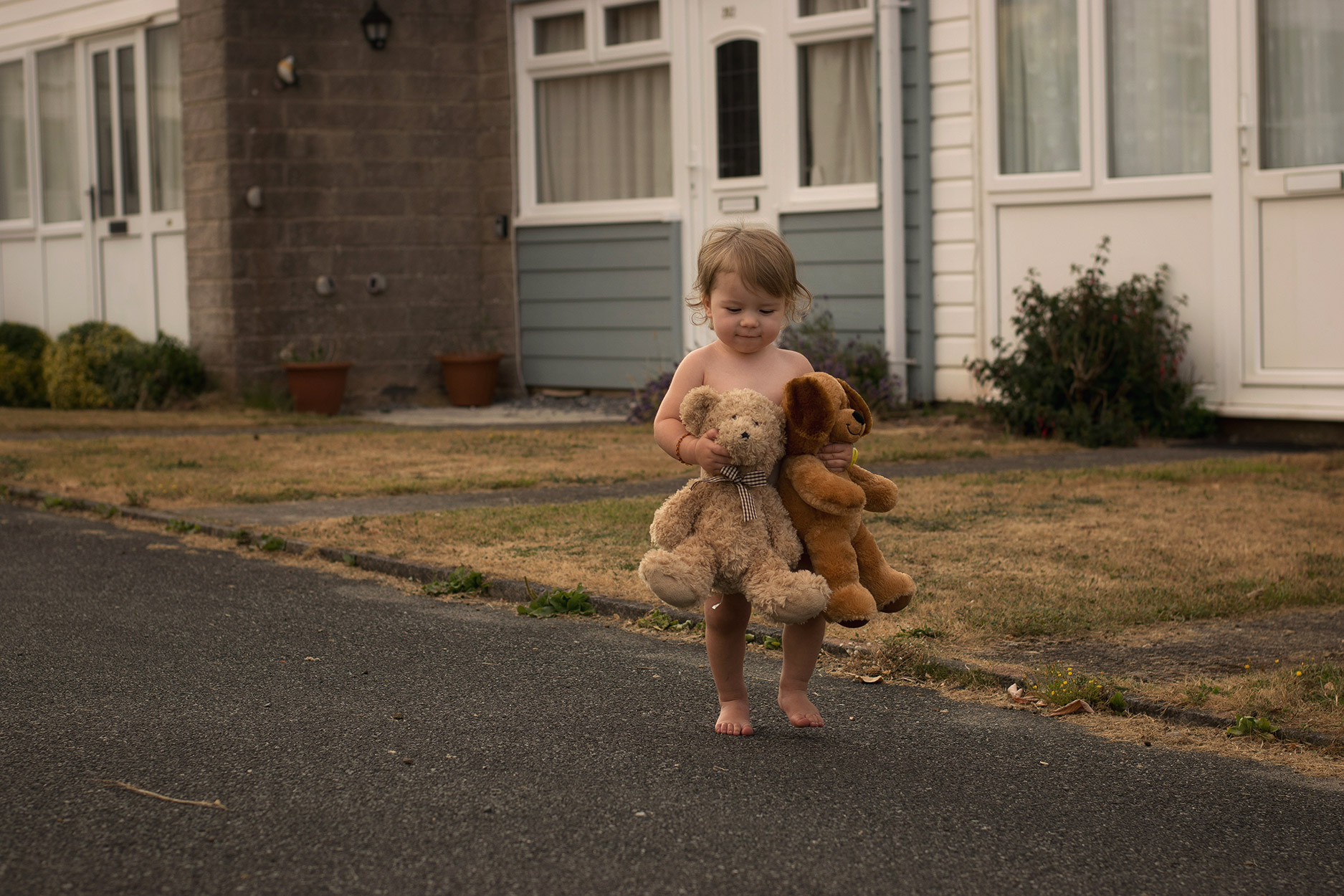 Toddler clutching teddy bear and dog soft toy walking on a warm Summer's evening outside the holiday home in Freshwater East, South Wales