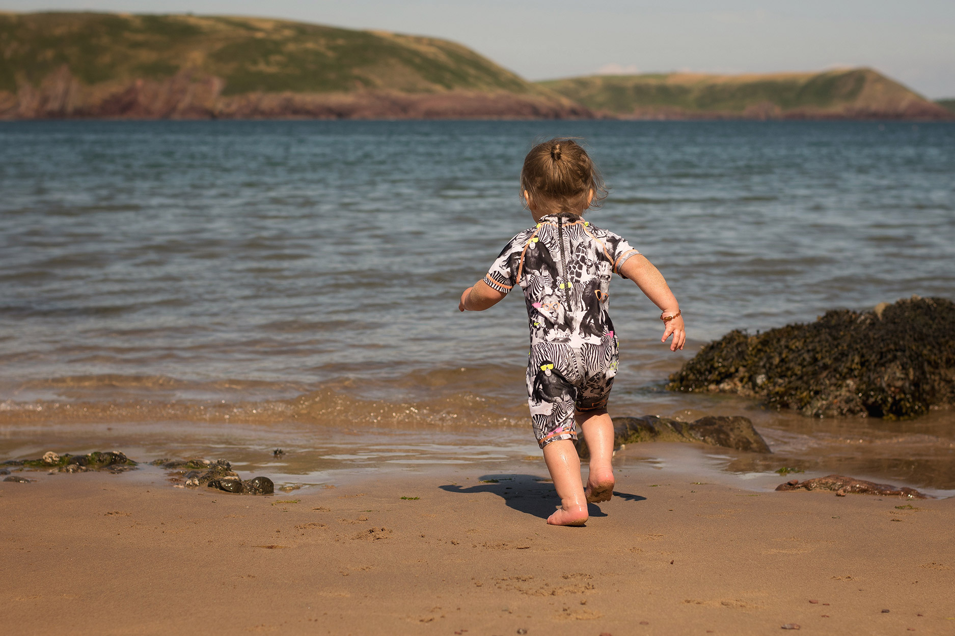 Toddler and older brother wearing twinning Next swimwear at the sandy beaches of Freshwater East, South Wales