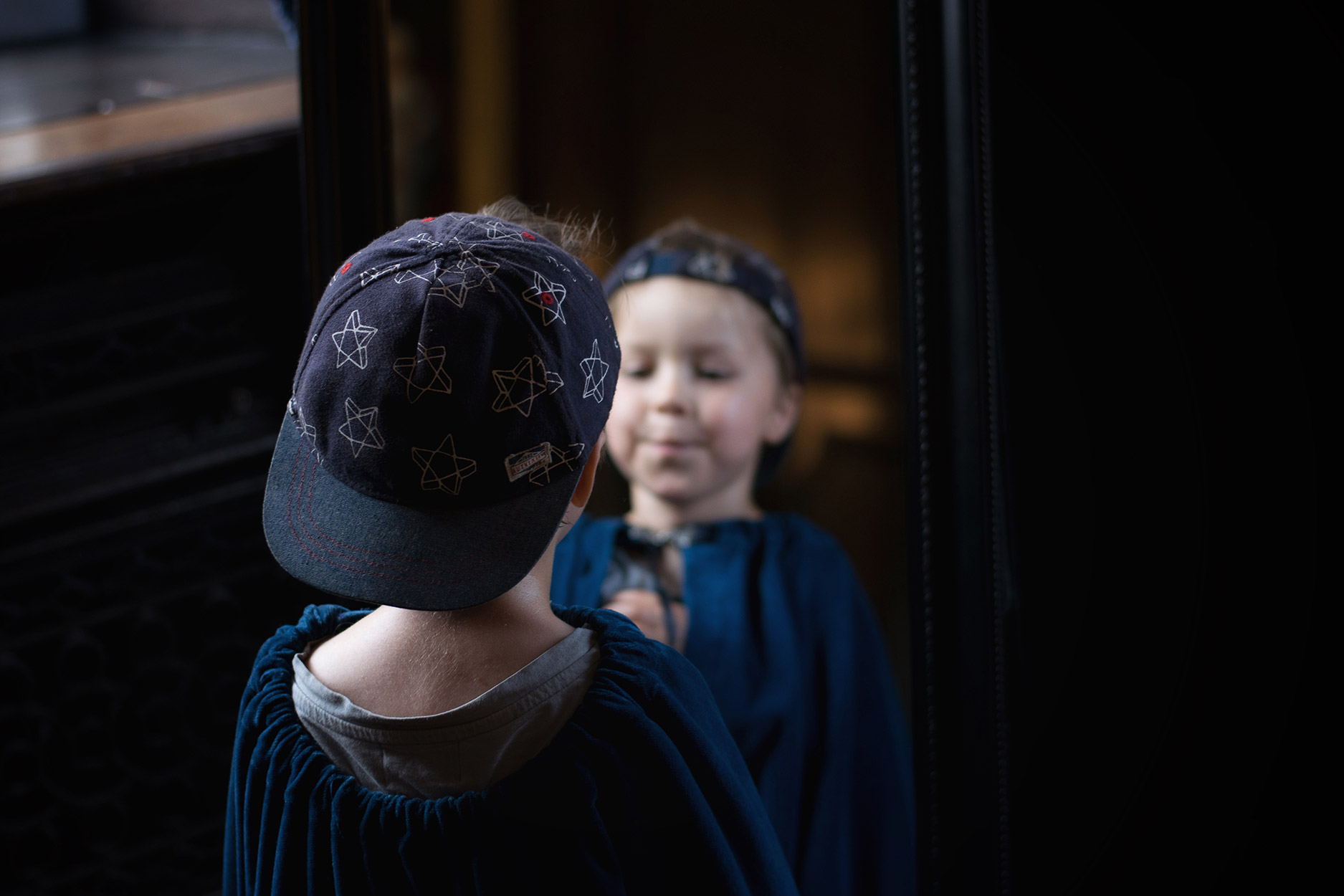 Boy dressing up in vintage clothes and cloaks at Tredegar House, National Trust in Newport, Wales