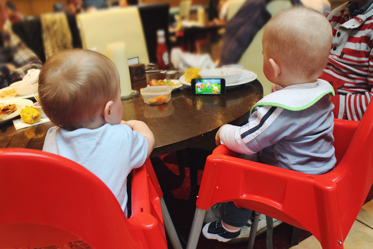 Young baby cousins in high chairs together at Sun Inn, Swindon