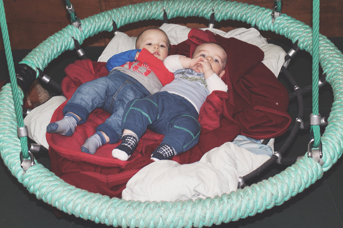 Young baby cousins in swing together at Roves Farm, Swindon